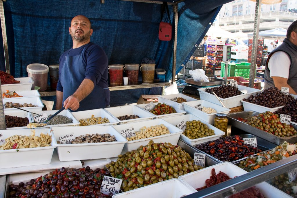 Olive vendor, Catania market - buying groceries was one of my travel saving tips