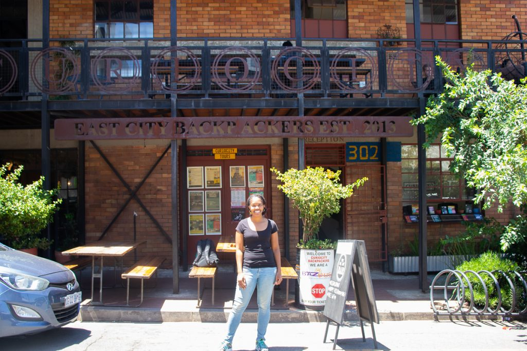 Me outside Curiocity Joburg - booking a hostel is another travel saving tip!